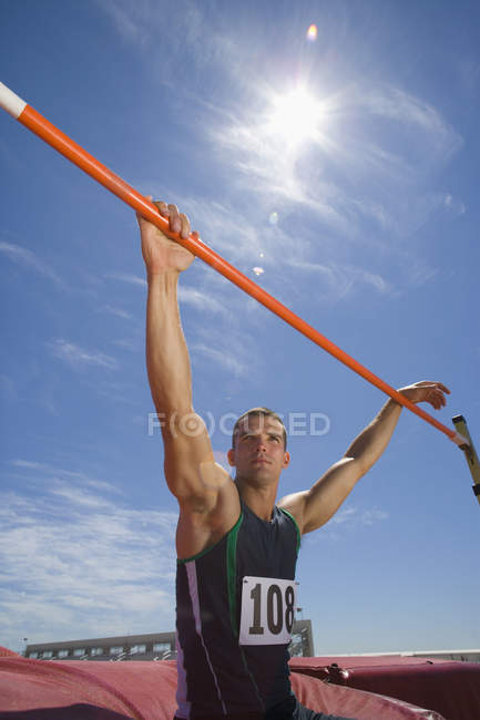 Young male athlete with hands on bar, low angle view (lens flare) — Stock Photo