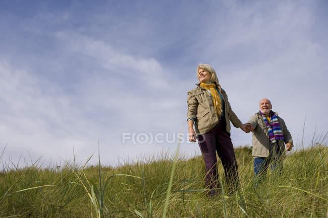 Vista de ângulo baixo do casal sênior de mão em mão na duna de areia sorrindo — Fotografia de Stock
