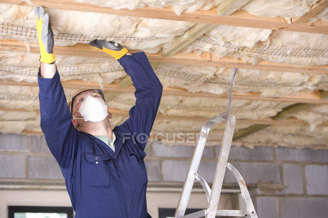 Man in protective mask installing ceiling — Stock Photo