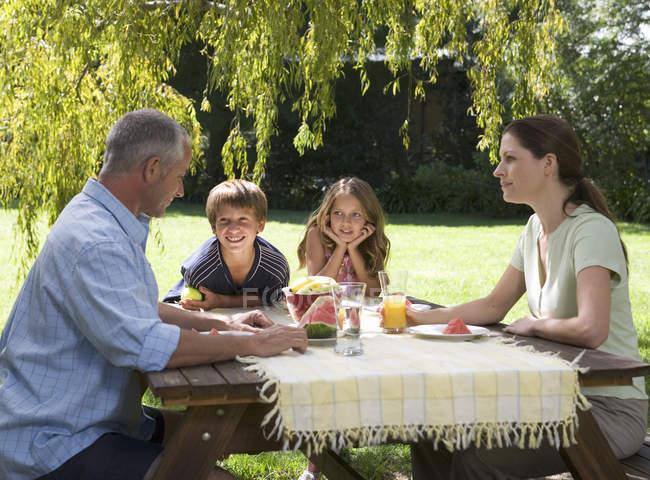 Family having lunch in the garden — Stock Photo