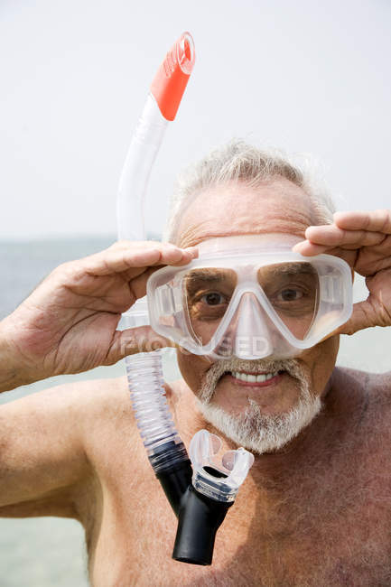Senior man with snorkel gear at the beach — Stock Photo