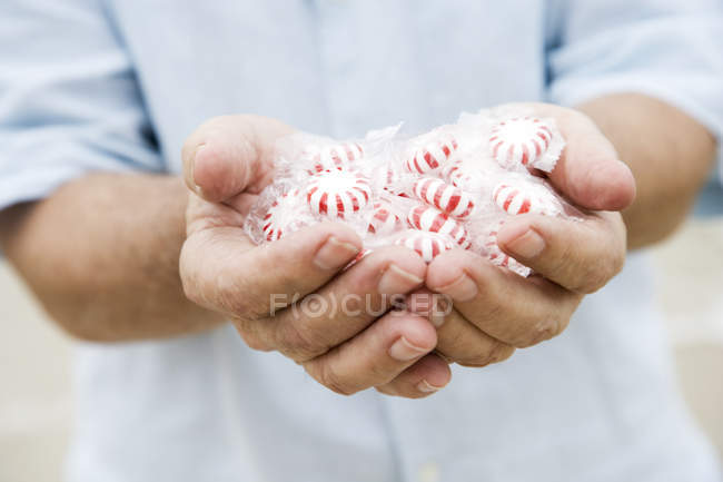 Senior man's hands holding candies — Stock Photo