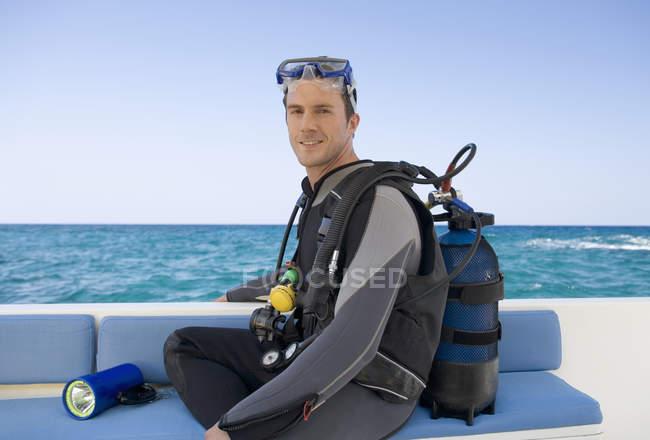 Un hombre sentado en un barco preparándose para bucear - foto de stock