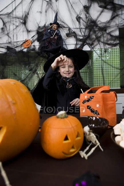 Petite fille en costume de sorcière lors d'une fête d'Halloween — Photo de stock