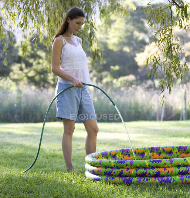Mother filling a paddling pool with a garden hose — Stock Photo