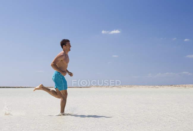 Um homem correndo na praia — Fotografia de Stock