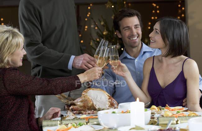 Heureuse familles lunettes sonnante au dîner — Photo de stock
