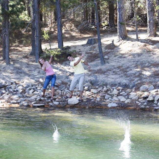 Молода пара, skimming каменів — стокове фото