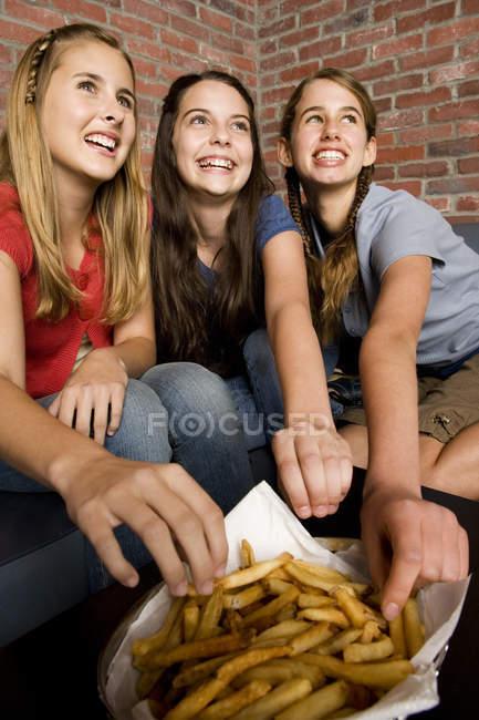 Drei Mädchen im Teenageralter teilen einen Teller mit Pommes frites — Stockfoto