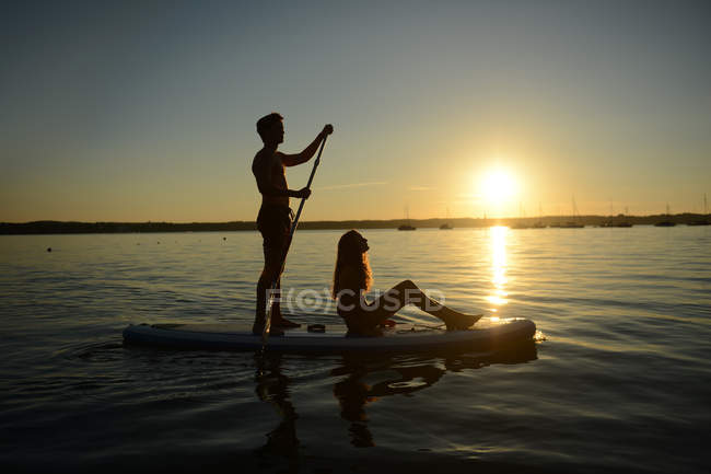 Casal adolescente rema embarque ao pôr do sol no lago de Starnberg, na Baviera, Alemanha, Europa — Fotografia de Stock