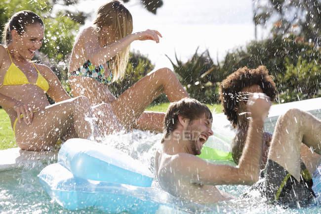 Vier Teenager Freunde, die Spaß in einem Schwimmbad — Stockfoto