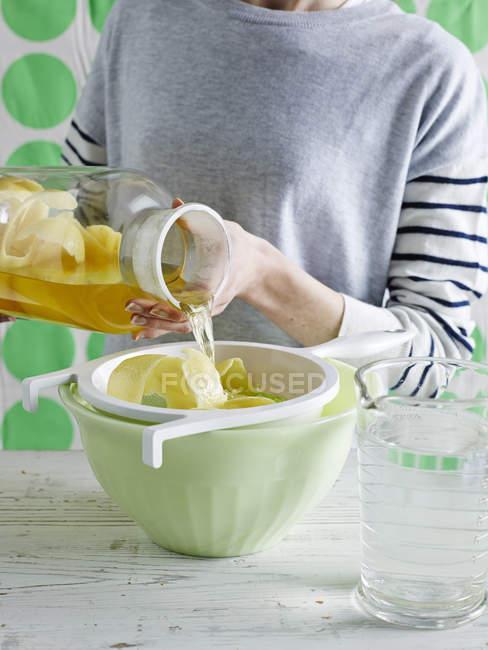 Des mains de femme battante thé glacé au citron — Photo de stock