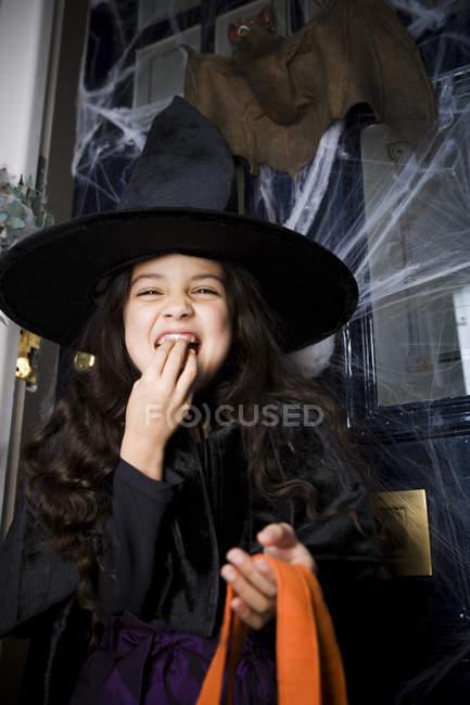 Jeune fille en costume de sorcière lors d'une fête d'Halloween, manger des bonbons — Photo de stock