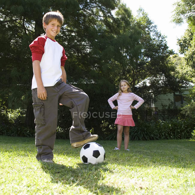 Young boy and girl playing with a football in a garden — Stock Photo