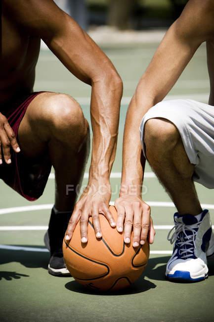 Zwei afrikanische Männer Knien nebeneinander auf einem städtischen Basketballplatz, Nahaufnahme — Stockfoto