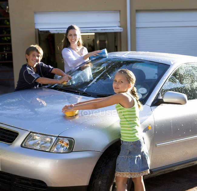 Mother and her children washing a car — Stock Photo