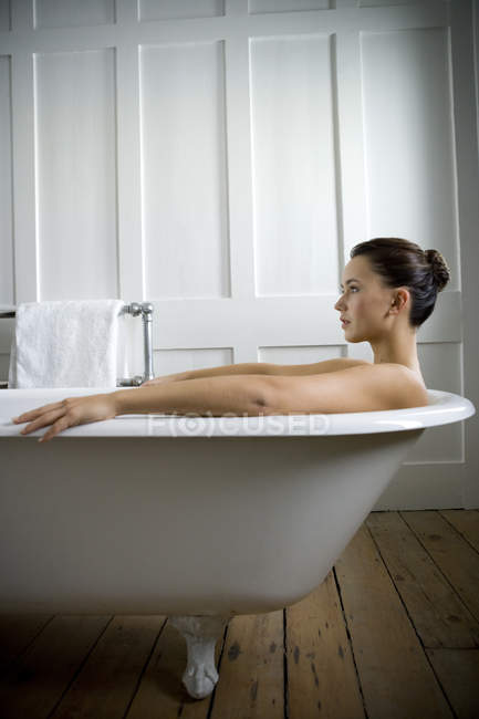 A young woman lying in a bath — Stock Photo