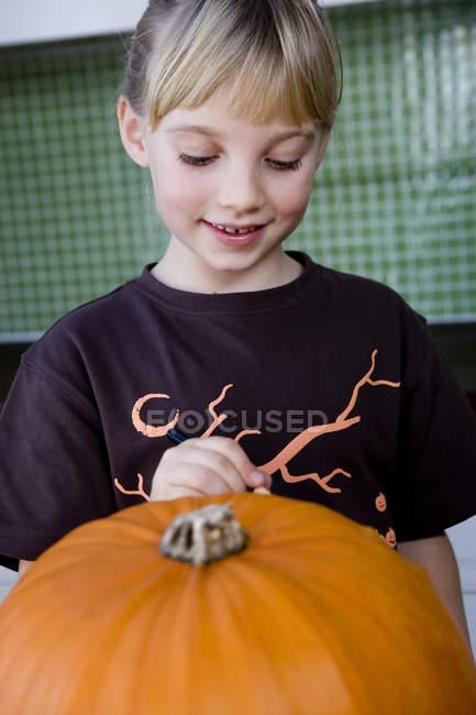 Petite fille, sculpter un visage dans une citrouille d'Halloween — Photo de stock