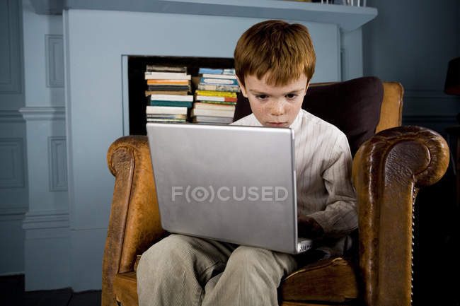 Boy sitting in armchair using laptop computer — Stock Photo