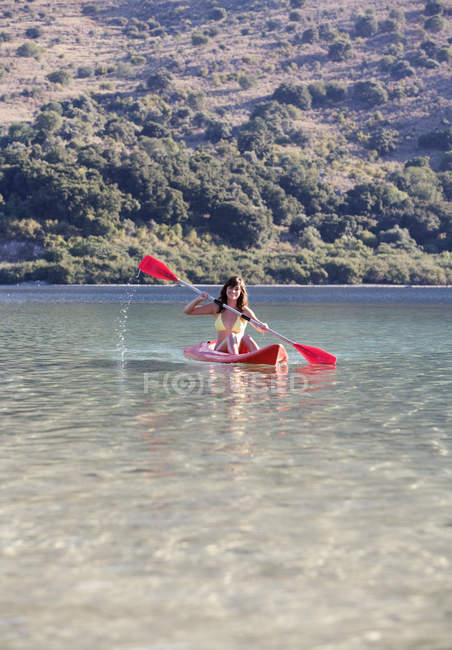 A woman canoeing on a lake — Stock Photo