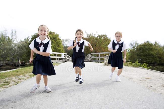 Drei SchülerInnen liefen eine Straße — Stockfoto