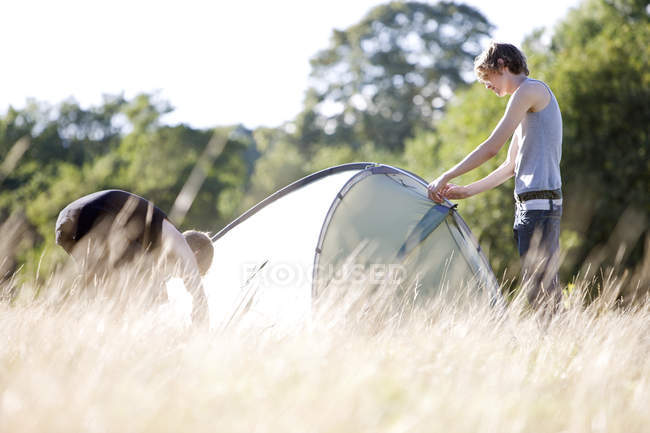 Two young men setting up a tent in a field — Stock Photo