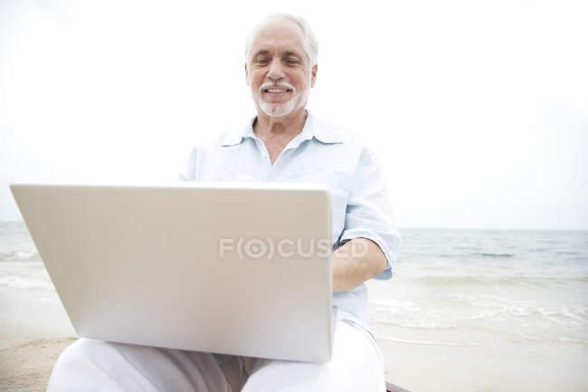 Uomo maggiore sulla spiaggia utilizzando un computer portatile — Foto stock