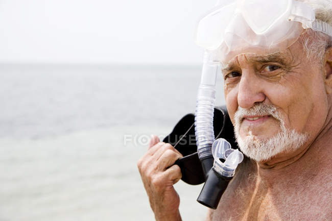 Senior man with snorkel gear and flippers at the beach — Stock Photo