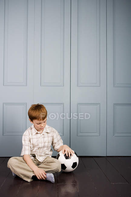 Little boy sitting on the floor with football — Stock Photo
