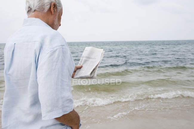 Senior man at the beach reading a newspaper — Stock Photo