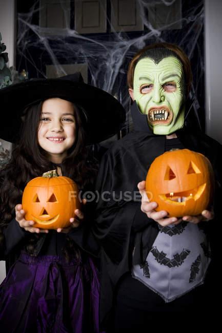 Enfants en costumes d'Halloween, tenant des citrouilles avec visages sculptés — Photo de stock