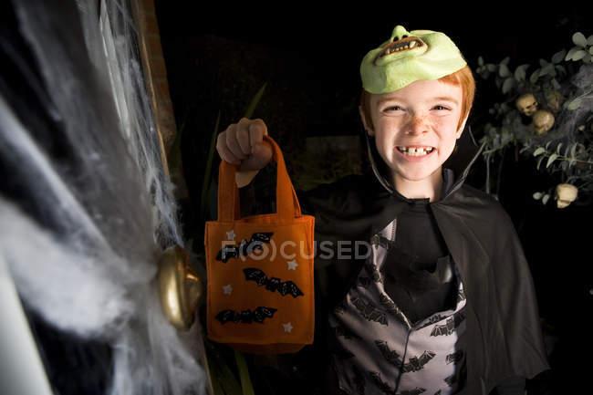 Garçon en costume lors d'une fête d'Halloween, tenant un sac parti orange — Photo de stock
