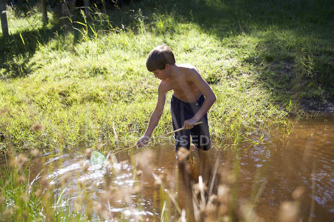A young boy with a fishing net — Stock Photo