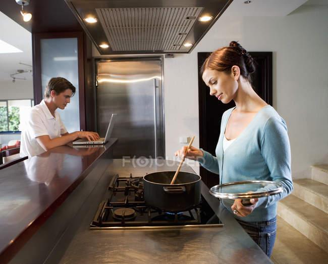 Donna che cucina nella cucina mentre un uomo che per mezzo del computer portatile — Foto stock