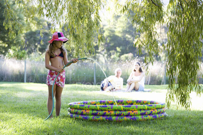 Young girl filling a paddling pool from a garden hose — Stock Photo