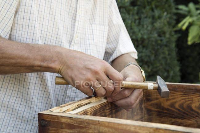 Mâles mains tenant le marteau et en caisse — Photo de stock