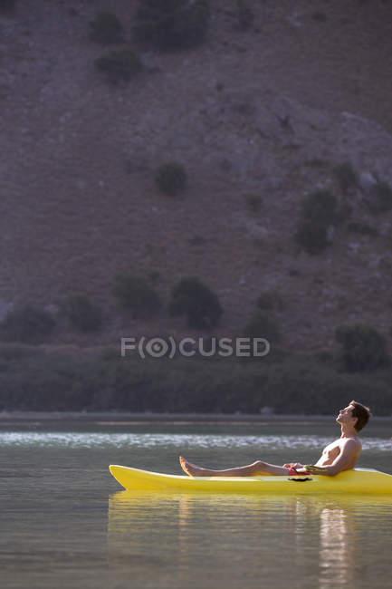 Um homem relaxando em uma canoa — Fotografia de Stock