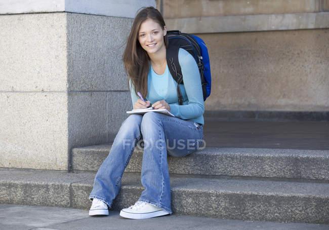 Ritratto di una ragazza studente seduto sui gradini e che osserva macchina fotografica — Foto stock