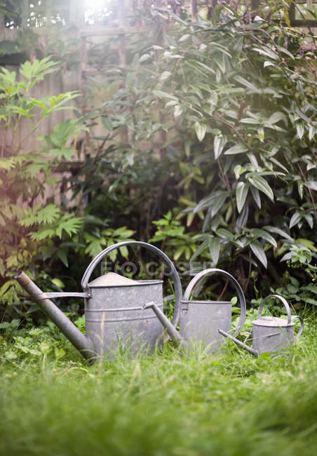 Watering cans on grass — Stock Photo