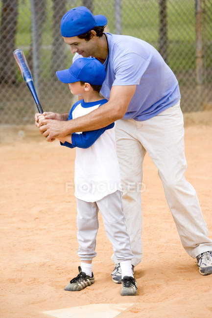 Young boy being taught how to swing a baseball bat — стокове фото