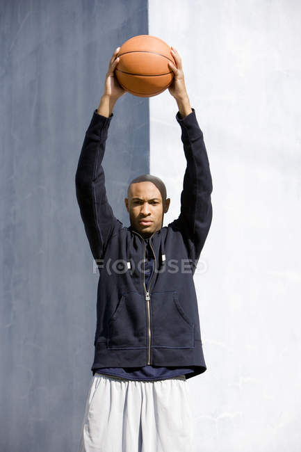 Portrait of young African American man holding a basketball above his head — Stock Photo