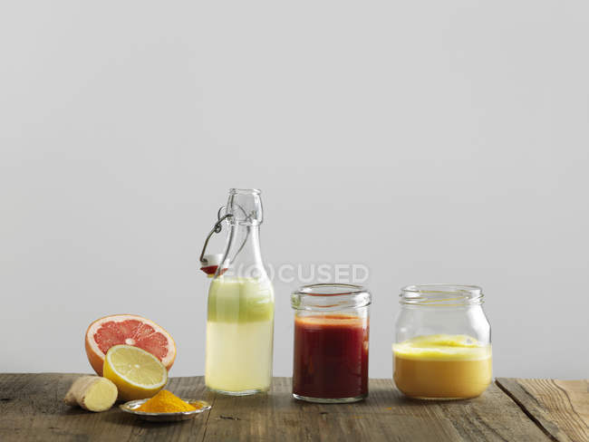 Fruit smoothies in glass bottle and jars, white background — Stock Photo