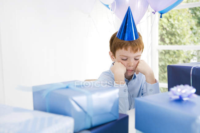 Boy looking sad at birthday party — Stock Photo