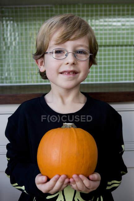 Petit garçon tenant une orange citrouille d'Halloween — Photo de stock