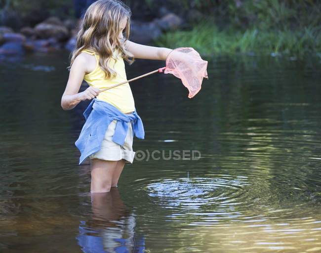 A young girl standing in a river with a fishing net — Stock Photo