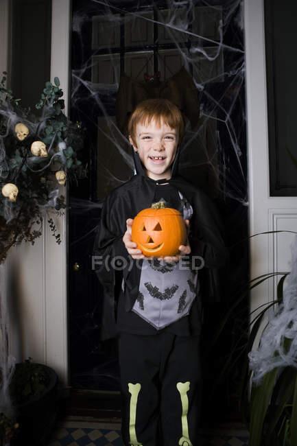 Garçon dans un costume de squelette à l'Halloween, tenant une citrouille avec un visage sculpté — Photo de stock