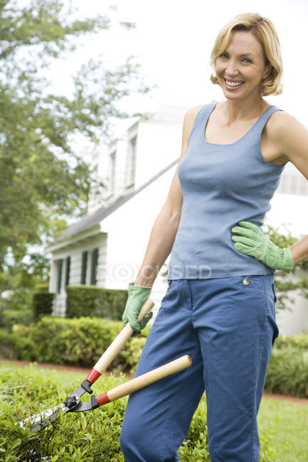 Woman with garden shears hand on hip — Stock Photo