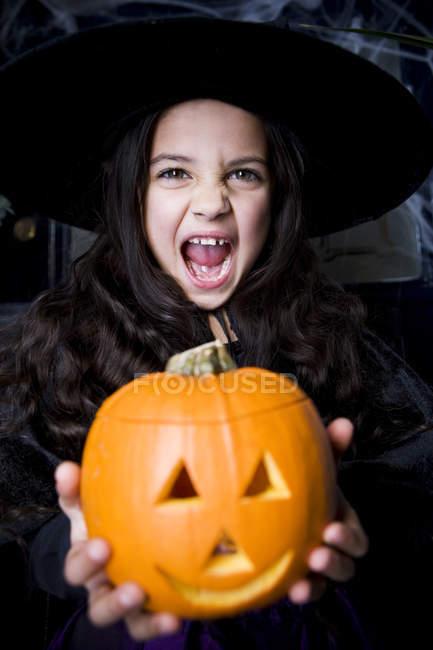 Jeune fille en costume de sorcière lors d'une fête d'Halloween, tenant une citrouille avec un visage sculpté — Photo de stock