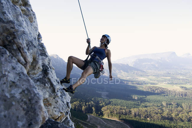A climber woman abseiling on rock — Stock Photo