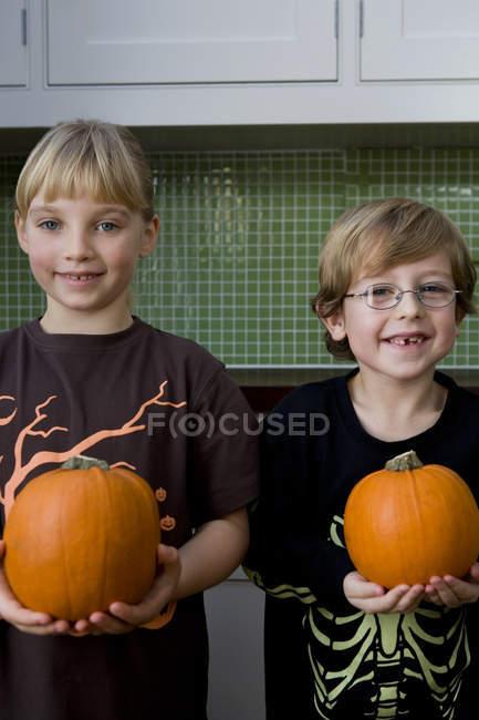 Deux enfants tenant des citrouilles d'Halloween orange — Photo de stock
